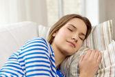 Smiling teenage girl sleeping on sofa at home — Stock Photo