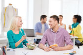 Smiling fashion designers having lunch at office — Stock Photo