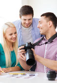 Smiling team with photocamera working in office — Stockfoto