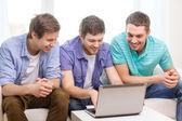 Amigos sorridentes com o computador portátil em casa — Fotografia Stock