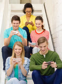 Smiling students with smartphone texting at school — Zdjęcie stockowe