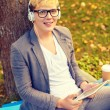 Smiling male student in eyeglasses with tablet pc — Stock Photo #47458295