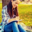 Smiling teenager writing in notebook — Stock Photo #47458465