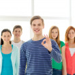 Students with teenager in front showing ok sign — Stock Photo #47458757