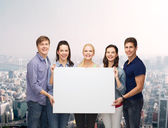 Group of standing students with blank white board — Foto Stock