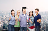 Group of students with diploma showing thumbs up — Stock Photo
