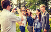 Teenagers taking photo with digital camera outside — Stock Photo
