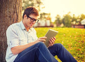 Smiling male student in eyeglasses with tablet pc — Stock Photo