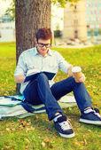 Livre de lecture d'adolescent avec emporter café — Photo