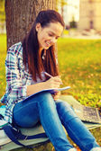 Smiling teenager writing in notebook — Foto Stock