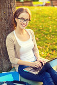 Smiling teenager in eyeglasses with laptop — Stock Photo