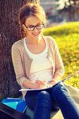 Smiling teenager in eyeglasses writing in notebook — Stock Photo