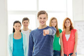 Students with teenager in front pointing at you — Stock Photo