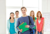 Smiling students with teenage boy in front — Stock Photo
