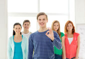Students with teenager in front showing ok sign — Stock Photo