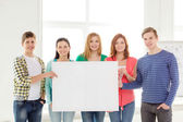 Students at school holding white blank board — Stock Photo