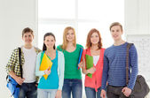 Smiling students with bags and folders at school — Foto Stock