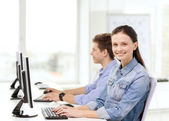 Two smiling students in computer class — Stock Photo