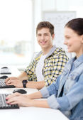 Smiling boy with girl in computer class at school — Stock Photo