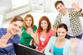 Group of smiling students waving hands at school — Stock Photo