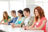 Smiling students with smartphones at school — Stock Photo
