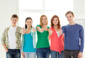 Smiling students at school showing thumbs up — Stock Photo