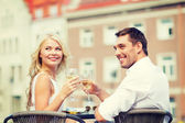 Smiling couple drinking wine in cafe — Foto Stock
