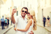 Smiling couple with smartphone in the city — Stock Photo