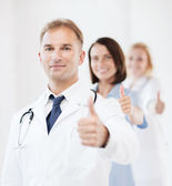 Doctor with stethoscope and colleagues — Stock Photo
