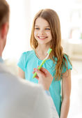 Male doctor giving toothbrush to smiling girl — Stock Photo