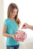 Smiling little girl holding piggy bank — Stock Photo