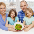 Happy family with two kids with salad at home — Stock Photo