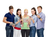 Smiling students using smartphones and tablet pc — Stock Photo