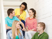 Smiling students with smartphone having discussion — Stock Photo