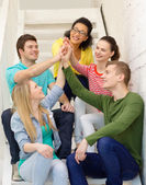 Smiling students making high five gesture sitting — Stock Photo