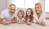 Pais e duas meninas, deitado no chão em casa — Fotografia Stock