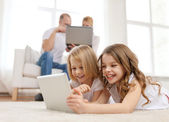 Smiling sister with tablet pc and parents on back — Foto Stock