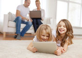 Smiling sister with tablet pc and parents on back — Stock Photo
