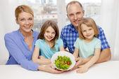 Família feliz com duas crianças com salada em casa — Fotografia Stock