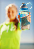 Woman showing a bottle of water — Stock Photo