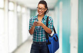 Student in eyeglasses with smartphone and bag — Stock Photo