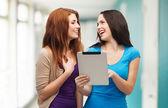 Два улыбающихся подростков с tablet pc компьютер — Стоковое фото