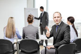 Businessman with team showing thumbs up in office — Stock Photo