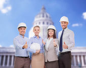 Happy business team in office showing thumbs up — Stock Photo