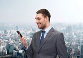 Young smiling businessman with smartphone — Stock Photo