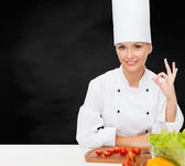 Female chef with vegetables showing ok sign — Stock Photo