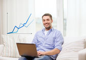 Smiling man working with laptop at home — Stock Photo