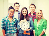 Group of students at school with clock — Stock Photo