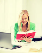 Smiling student girl reading book in college — Stock Photo