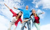 Group of teenagers spreading hands — Stock Photo